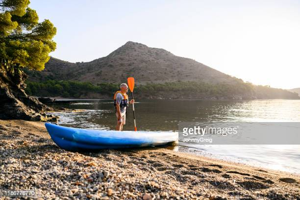 active senior male standing next to kayak with paddle - mediterranean sea stock pictures, royalty-free photos & images