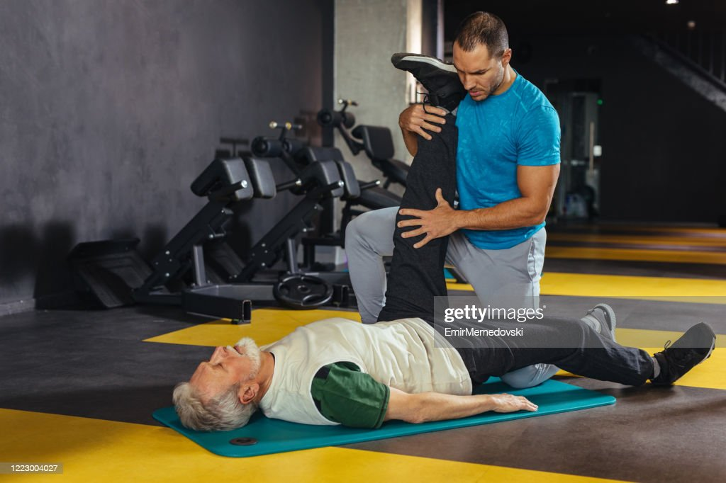Active senior male stretching in the health club assisted by personal trainer : Stock Photo