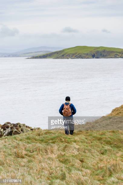 active senior man alone on cliffs in dumfries and galloway looking out at the sea - johnfscott stock pictures, royalty-free photos & images