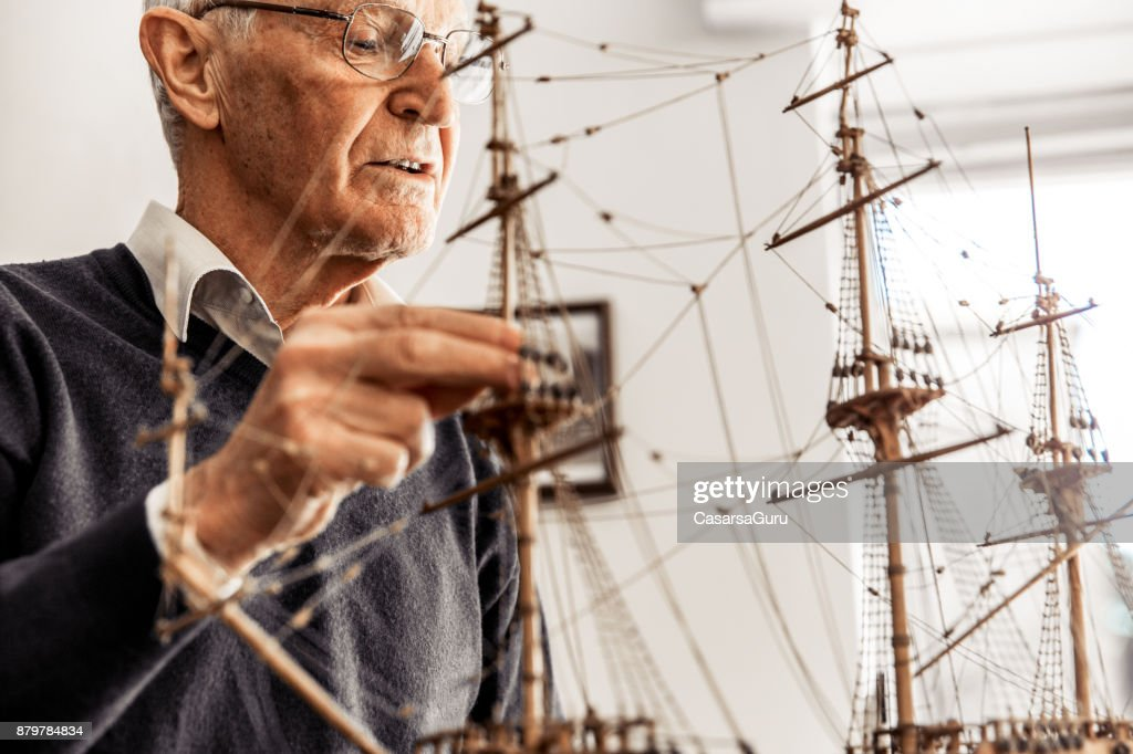 Active Senior Man Constructing a Boat Model : Stock Photo