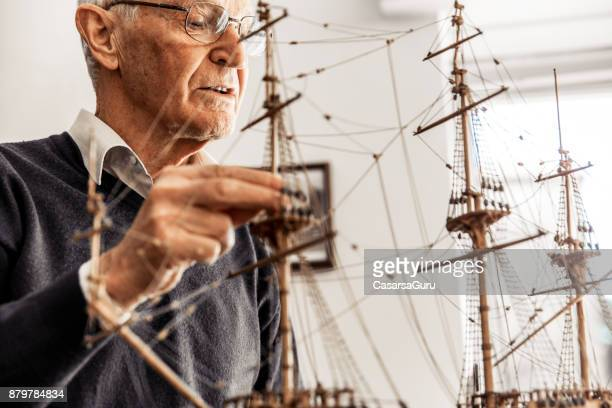 active senior man constructing a boat model - model building stock photos and pictures