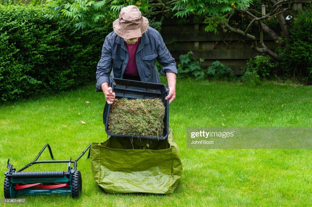Active senior man emptying a grass box : Stock Photo