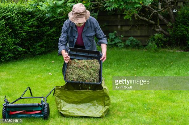 active senior man emptying a grass box - johnfscott stock pictures, royalty-free photos & images