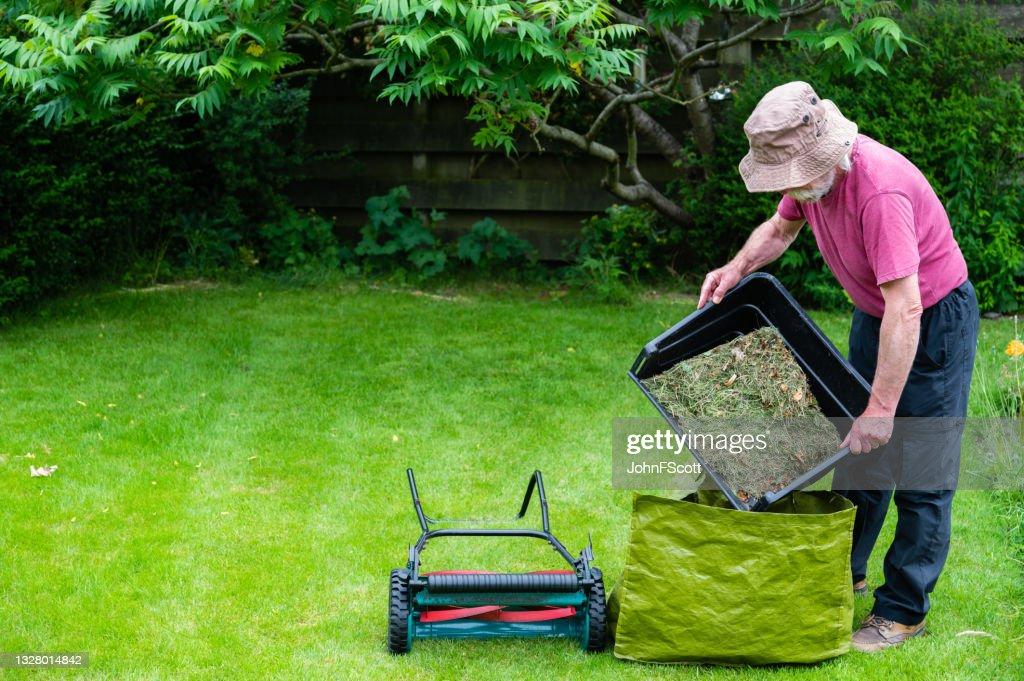 Active senior man emptying a mower grass box : Stock Photo