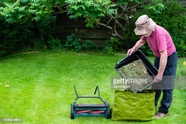 active senior man emptying a mower grass box - johnfscott stock pictures, royalty-free photos & images