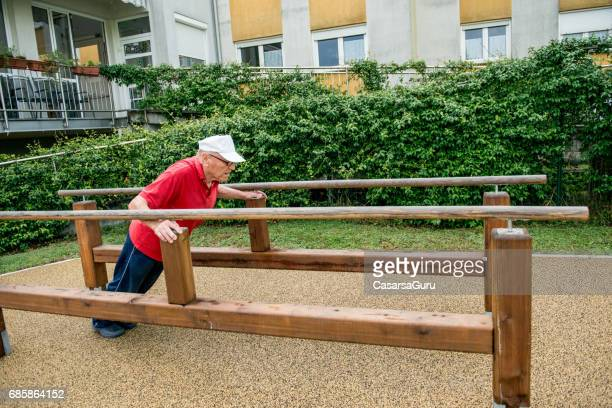 active senior man excersing on the barre at the nursing home - residential care stock photos and pictures