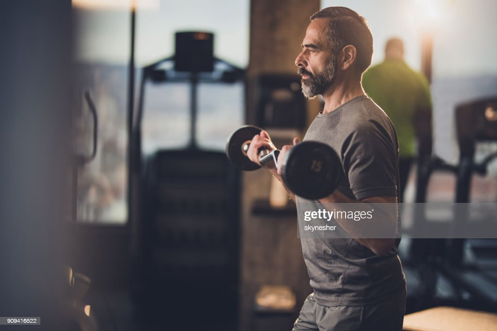 Active senior man having strength exercise with barbell in a gym. : Stock Photo