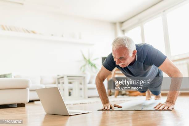 active senior man home exercising with online coach - push ups stock pictures, royalty-free photos & images