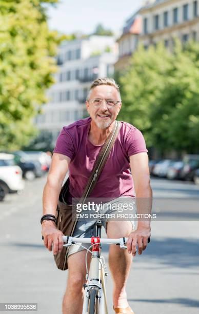 active senior man in his early 60s enjoys city life in summer. - aktiver lebensstil stock-fotos und bilder