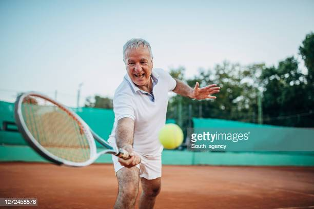 active senior man playing tennis on the outdoor tennis court - tennis player stock pictures, royalty-free photos & images
