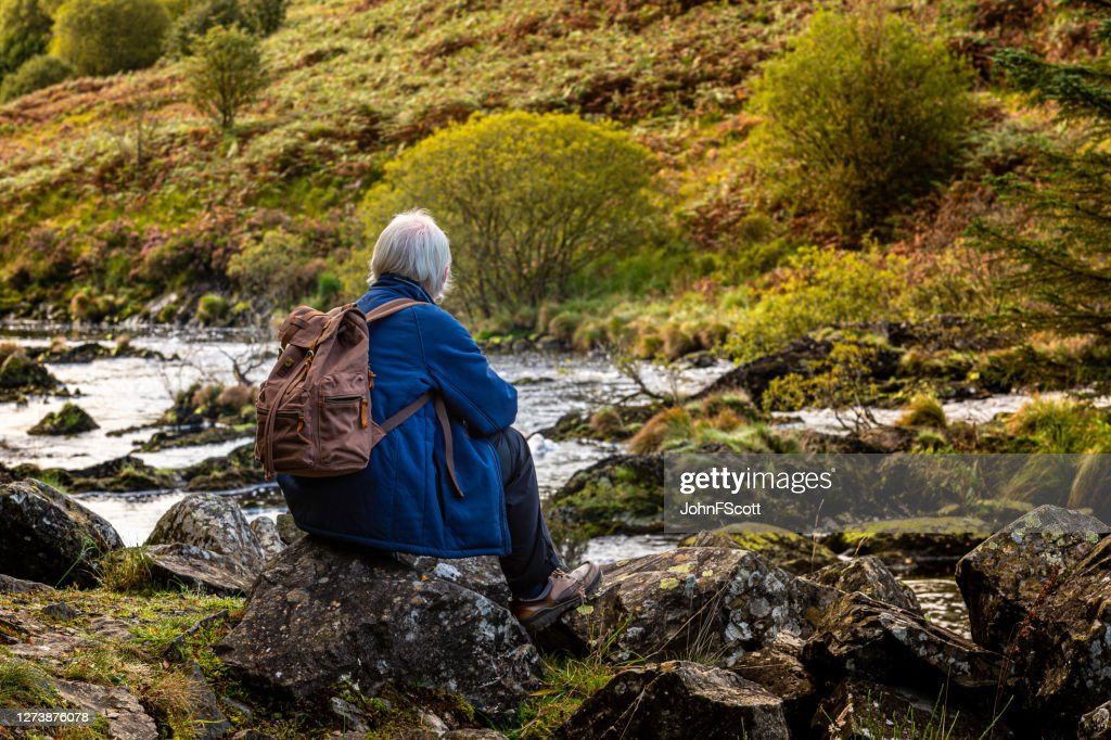 Active senior man sitting on a rock beside a Scottish river in rural south west Scotland. : Stock Photo