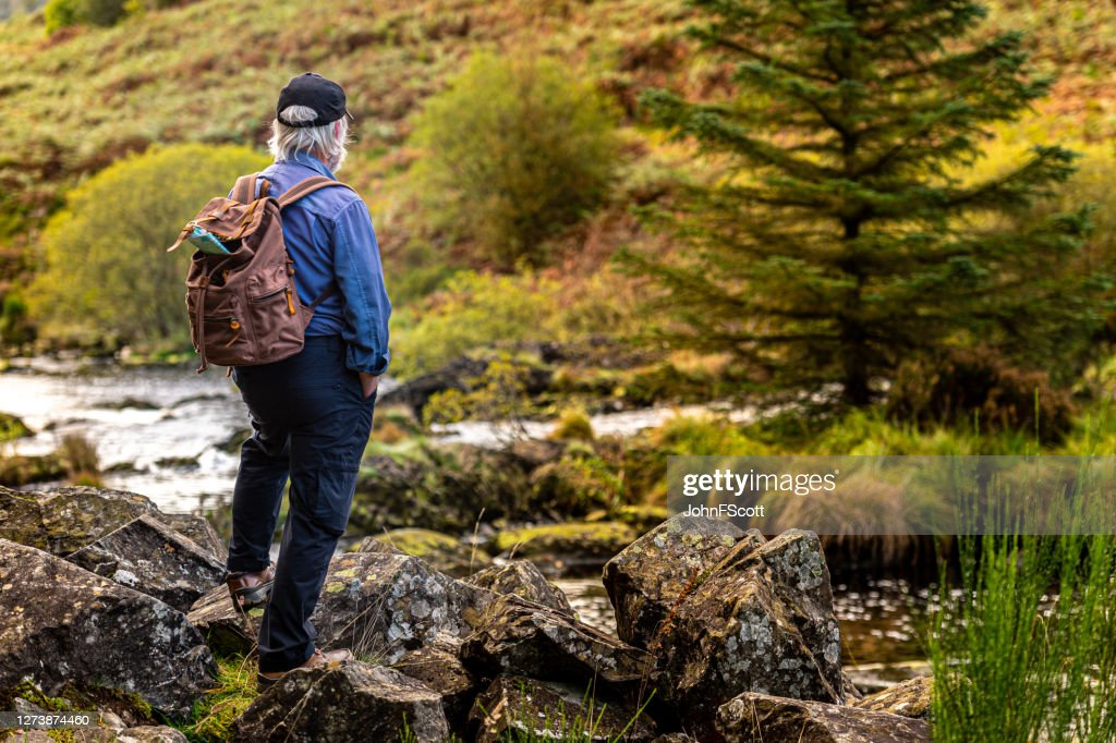 Active senior man taking a break to stand on a rock beside a Scottish river in rural south west Scotland. : Stock Photo