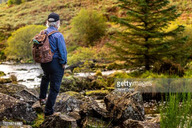 active senior man taking a break to stand on a rock beside a scottish river in rural south west scotland. - johnfscott stock pictures, royalty-free photos & images