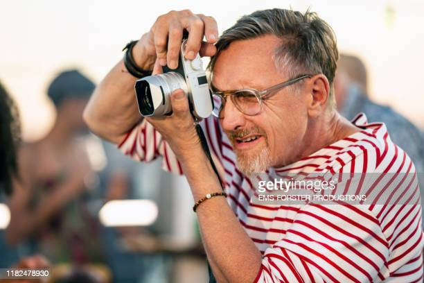active senior man taking pictures of people of a summer after work party - fotograf stock-fotos und bilder