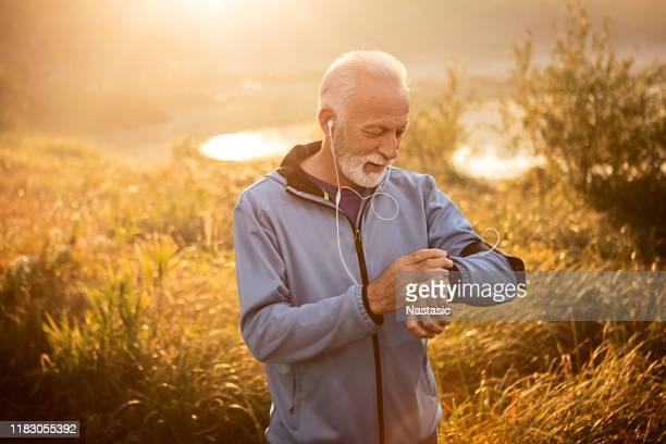 心拍数を測定するスマートウォッチを使用したアクティブシニアマン - スマートウォッチ ストックフォトと画像