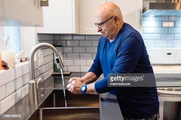 "active senior man washing hands in kitchen sink. - ""martine doucet"" or martinedoucet imagens e fotografias de stock"