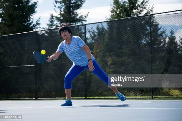 active senior playing pickleball at a public court - racquet stock pictures, royalty-free photos & images