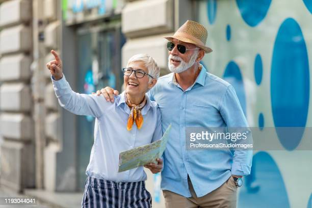 active senior tourists are walking through the city streets with map - studio city stock pictures, royalty-free photos & images