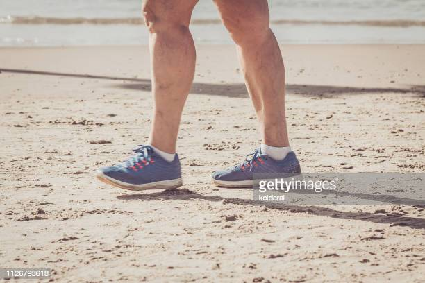 active senior walking on the sandy beach - knee replacement surgery stock pictures, royalty-free photos & images