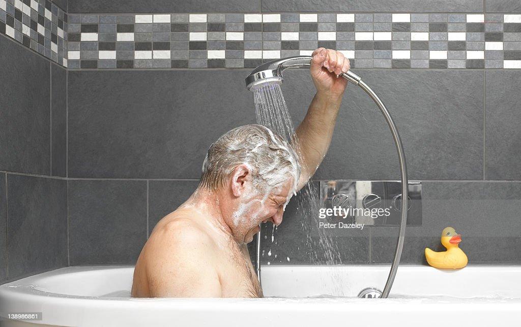 Active senior washing in bath : Stock Photo