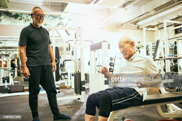 active senior who training at fitness club.exercising his muscles.son encourages father. - pep talk stock pictures, royalty-free photos & images