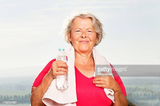 active senior woman after training with bottle of water - fat old lady stock photos and pictures