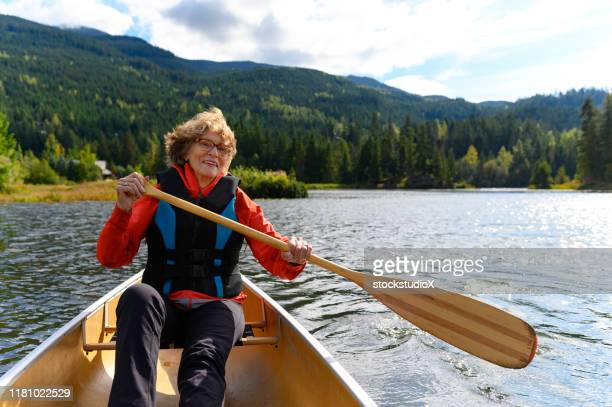 active senior woman canoeing on vacation - whistler british columbia stock pictures, royalty-free photos & images