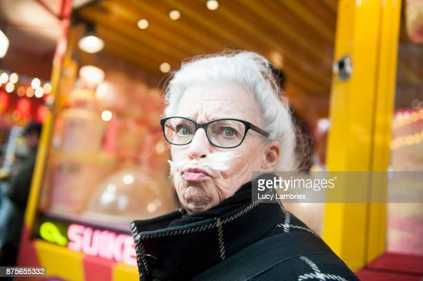 Active senior woman enjoying cotton candy at the fair in Amsterdam