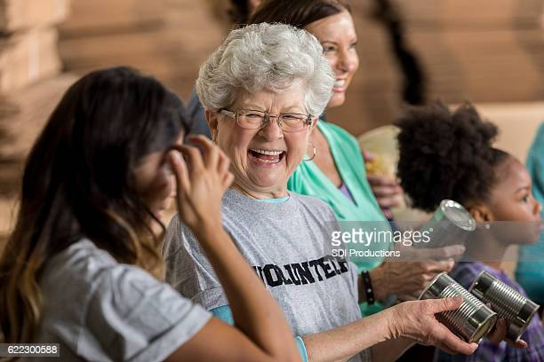 active senior woman enjoys volunteering at food bank - volunteer stock pictures, royalty-free photos & images