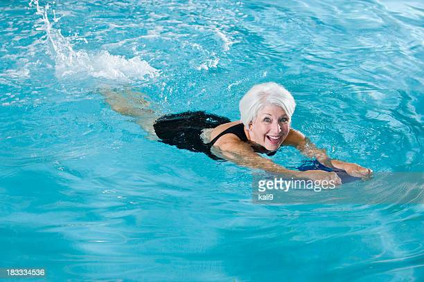 Active senior woman exercising in swimming pool