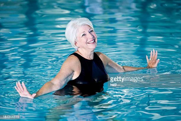 Active senior woman exercising in swimming pool