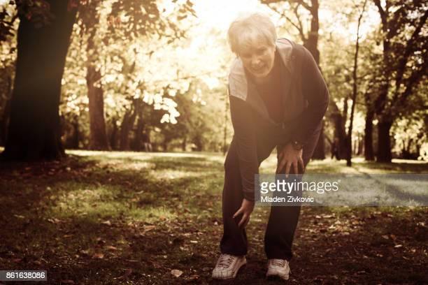 Mujer senior activa teniendo dolor en la rodilla después del ejercicio.