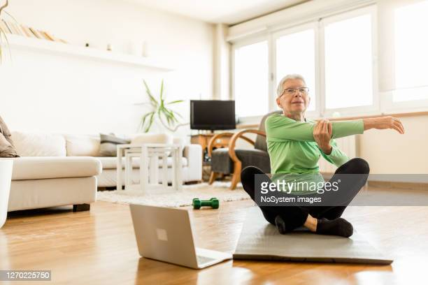 active senior woman home exercising with online coach - relaxation exercise stock pictures, royalty-free photos & images