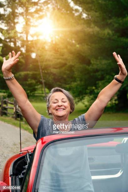 Active senior woman in convertible car in summer.