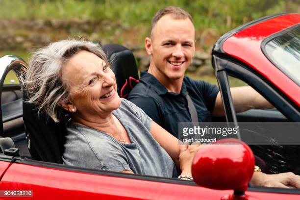 active senior woman in convertible car with adult son. - domestic car stock pictures, royalty-free photos & images