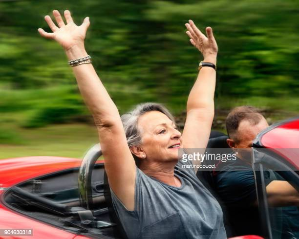Active senior woman in convertible car with adult son.