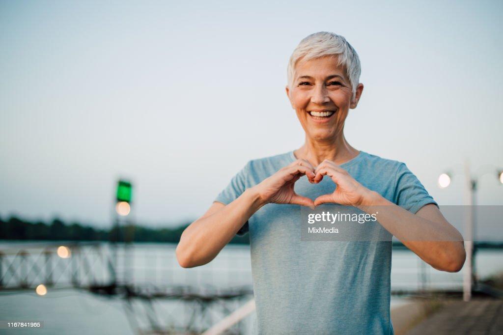 Aktive Seniorin macht ein Herz mit ihren Händen : Stock-Foto