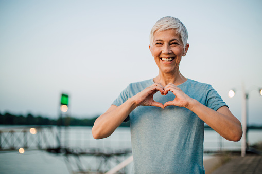 Active senior woman making a heart with her hands 1167841965