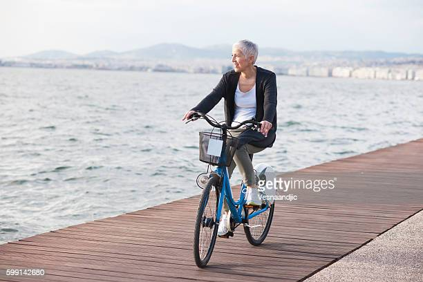 Active senior woman riding bicycle in the city