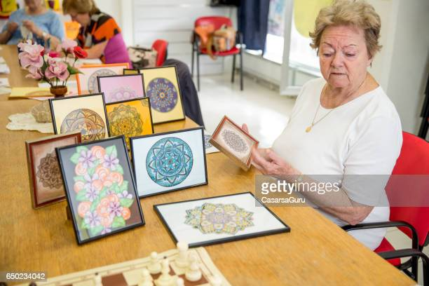 Active Senior Woman Showing Hand Made Art Craft In The Community Center