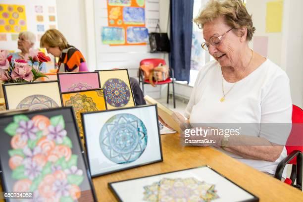 Femme Senior active montrant artisanal artisanat d'Art dans le centre de la communauté