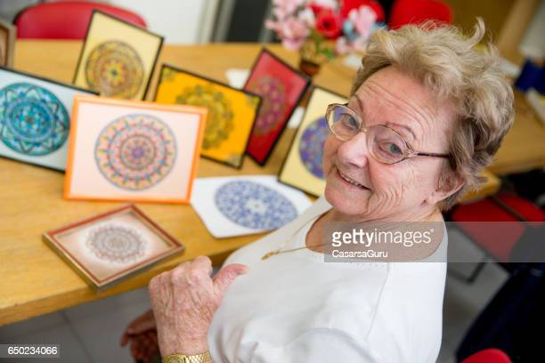 active senior woman showing hand made art craft in the community center - community centre stock pictures, royalty-free photos & images