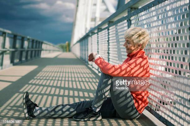 active senior woman sitting on floor resting after running looking at smart watch - wearable computer stock pictures, royalty-free photos & images