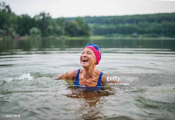 active senior woman standing in lake outdoors in nature, laughing. - lifestyle stock pictures, royalty-free photos & images