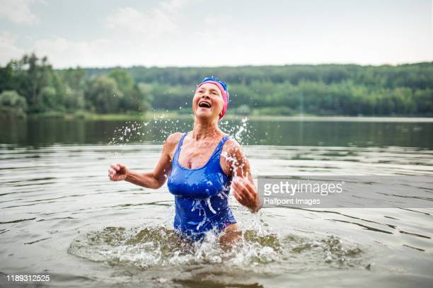 active senior woman standing in lake outdoors in nature, splashing water. - disruptaging stock pictures, royalty-free photos & images