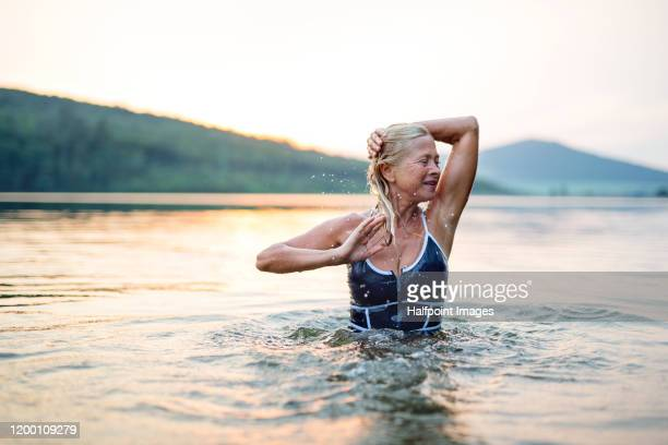 active senior woman standing in water in lake outdoors in nature. copy space. - estilo de vida ativo imagens e fotografias de stock