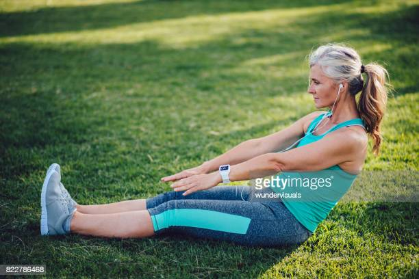 active senior woman stretching and listening to music in park - older woman legs stock photos and pictures