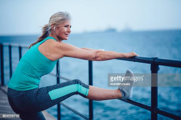 active senior woman warming up by the sea for jogging - stretching stock photos and pictures