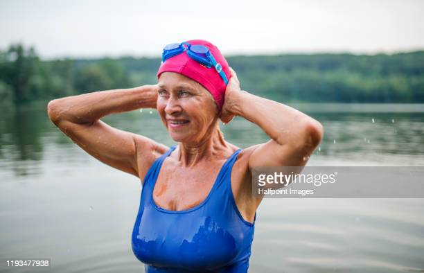 active senior woman with cap and goggles standing in lake outdoors in nature. copy space. - 溜水 ストックフォトと画像