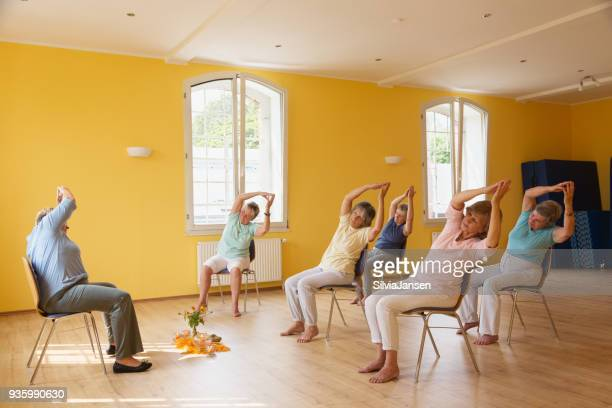 active senior women in yoga class exercisig on chairs, - chair stock pictures, royalty-free photos & images